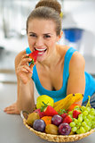 Closeup on young woman with fruits plate eating strawberry