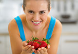 Happy young woman showing strawberries