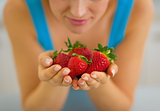 Closeup on young woman enjoying strawberries