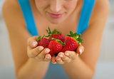 Closeup on young woman enjoying strawberries