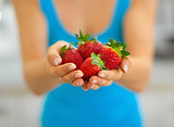 Closeup on young woman showing strawberries