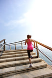 woman running on stone stairs seaside