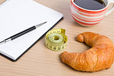 diet concept . croissant and measuring tape