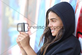 Skater style teen girl reading happy her smart phone