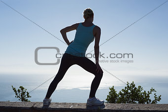 Fit woman stretching her legs looking out to sea