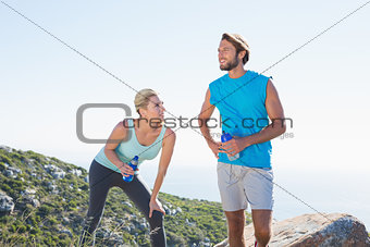 Fit couple standing holding water bottles