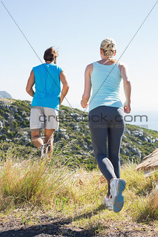 Fit couple jogging on a country trail