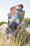 Fit couple taking a break at summit smiling at each other