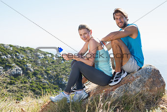 Fit couple taking a break at summit smiling at camera