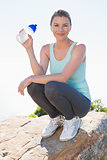 Fit blonde sitting at summit holding water bottle smiling at camera