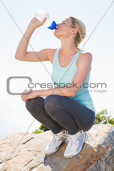 Fit blonde sitting at summit drinking from water bottle