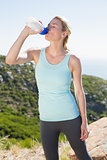 Fit blonde taking a break at summit drinking water