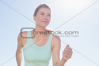 Fit woman jogging and smiling