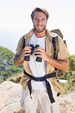 Handsome hiker holding binoculars on mountain trail