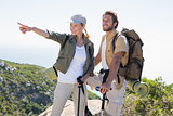 Hiking couple pointing and looking at mountain summit