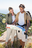 Hiking couple reading map at mountain summit