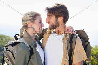 Attractvie hiking couple hugging on mountain trail