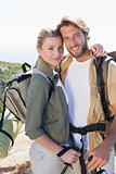 Attractive hiking couple smiling at camera on mountain trail