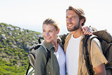 Attractive hiking couple hugging on mountain trail