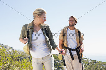 Attractive hiking couple walking on mountain trail