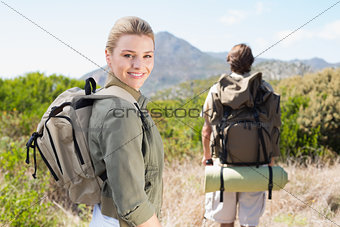Attractive hiking couple walking on mountain trail woman smiling at camera