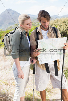 Attractive hiking couple reading the map on mountain trail