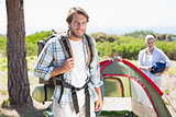 Attractive man smiling at camera while partner pitches tent