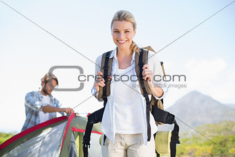 Attractive hiking blonde smiling at camera while partner pitches tent