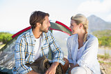 Attractive hiking couple smiling at each other outside their tent