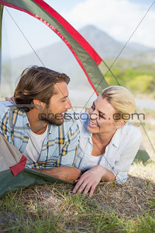 Attractive couple smiling at each other from inside their tent
