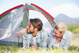 Attractive couple lying in their tent looking at something