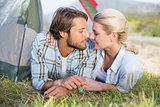 Attractive couple lying in their tent about to kiss