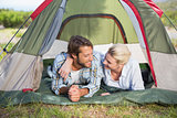 Attractive couple lying in their tent smiling at each other