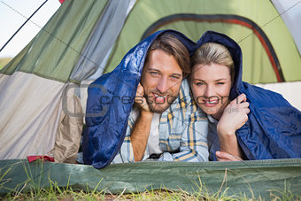 Attractive couple lying in their tent smiling at camera