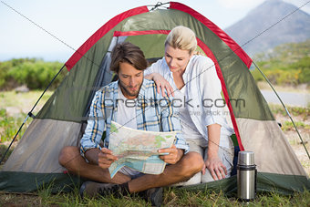 Attractive couple sitting by their tent reading map