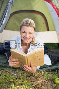 Attractive happy blonde lying in tent holding book
