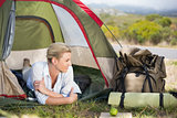 Attractive happy blonde lying in tent
