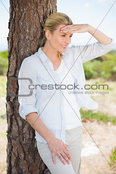 Attractive happy blonde standing by tree