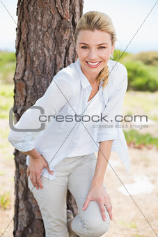 Attractive happy blonde standing by tree smiling at camera