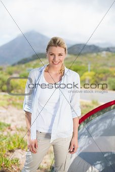 Attractive blonde standing by tent smiling at camera