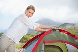 Attractive blonde setting up her tent