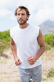 Attractive man jogging on mountain trail