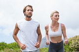 Attractive couple jogging on mountain trail