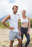 Attractive fit couple standing on mountain trail smiling at camera
