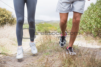 Fit couple jogging on mountain trail