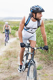 Fit attractive couple cycling on mountain trail