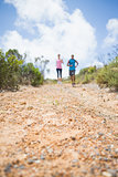 Fit couple jogging down mountain trail