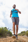 Fit man jogging down mountain trail