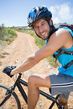 Fit man cycling up mountain trail smiling at camera