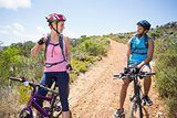Fit couple cycling down mountain trail